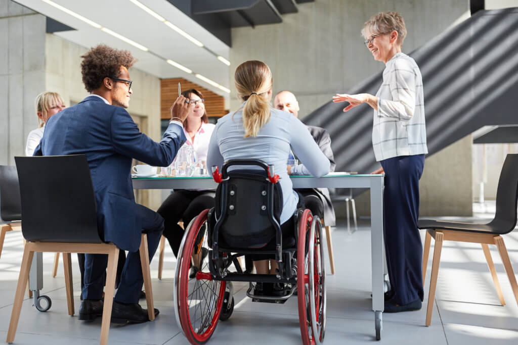 Business people with woman in wheelchair at meeting for project planning at table